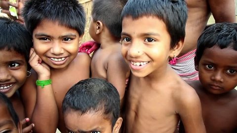 Village children in India smile, laugh and fool around in front of the camera, close up, narrow depth of field