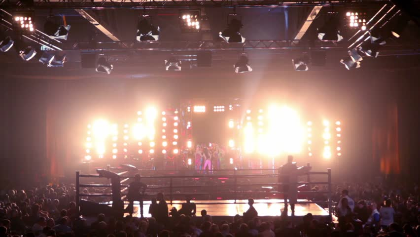 Lot of people in large hall on fighting event, girls dance on stage with bright illumination