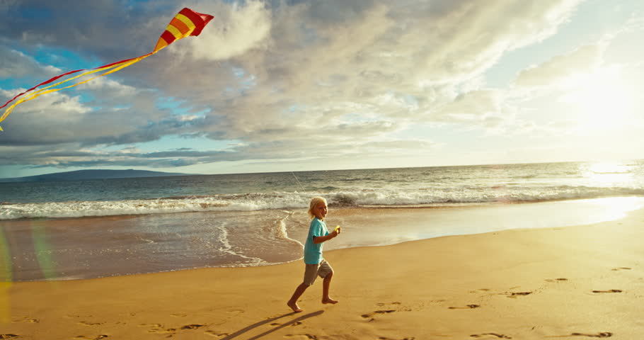 Young boy playing with kite on the beach | Shutterstock HD Video #18597356
