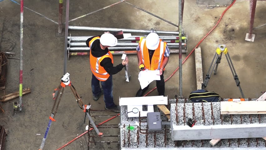 Aerial view of two unrecognized civil engineers inspecting construction site. Building