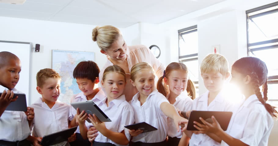 Teacher teaching kids on digital tablet in classroom at school 4k