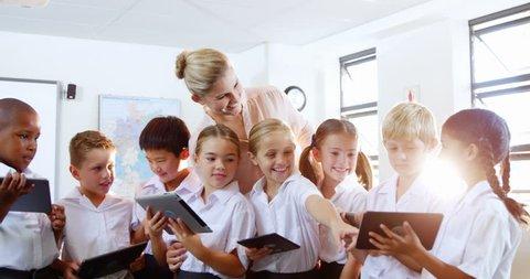 Teacher teaching kids on digital tablet in classroom at school 4k