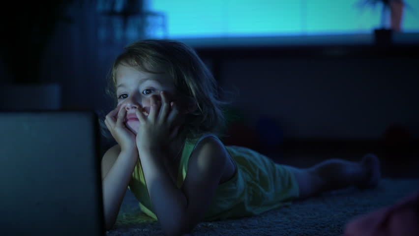 A little girl watches cartoons in the computer late in the evening.