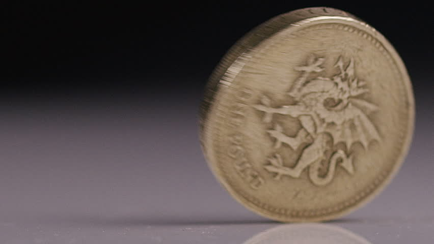 British One pound Sterling coin spinning, in slow motion