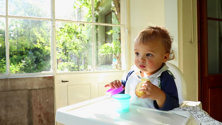 afe3c9818c7d Close up of adorable cute baby toddler blonde boy on high chair. Portrait  of baby eating cake and playing with baby toys