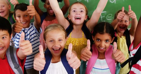 Portrait of group of diverse school kids showing thumbs up in classroom at school 4k