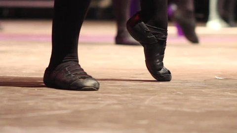 Woman doing Irish dance with traditional step shoes. Close up of female dancing feet on stage. Music, tradition and culture of Ireland. Celtic show on wooden floor