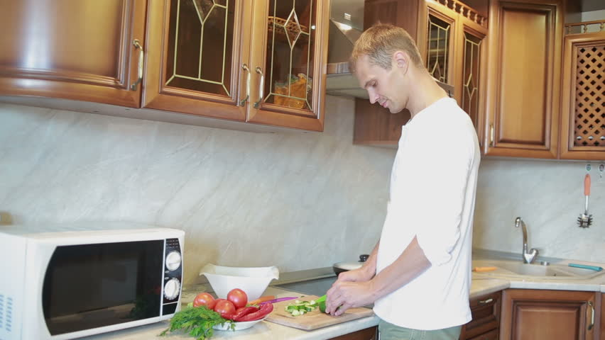 Smiling Man Preparing Salad In The Kitchen Hd Stock Clip