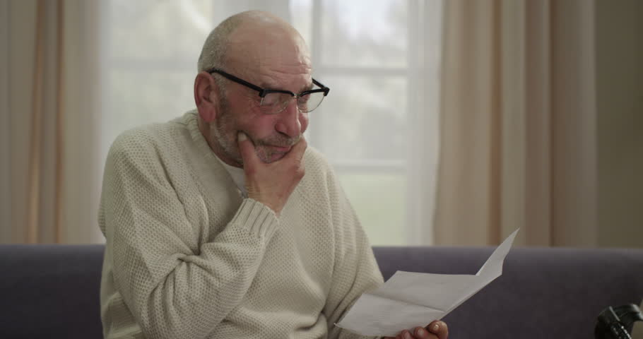 Elderly man reading the sad news of the letter and painful sigh. He has his hand on his  chest. | Shutterstock HD Video #18756707
