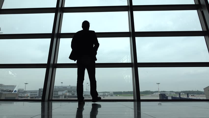 Man come and stand at full height, gaze out airport terminal window, silhouette view. Empty aeroport field outside, hipster person look out while waiting for boarding gate open, VKO lounge hall