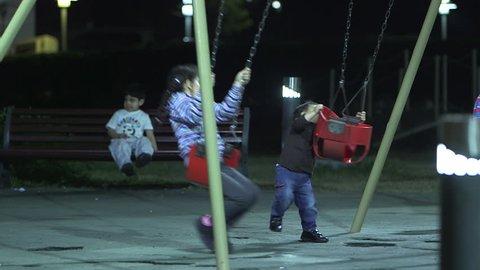Abu dhabi, uae - mcu night shot of emirati children at a swing set in a  children's park  (abu dhabi, uae-2013)