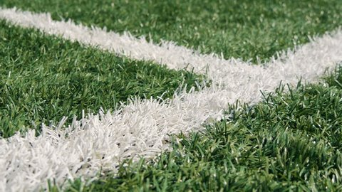 Close up of the out of bounds line on a turf football field. Green grass