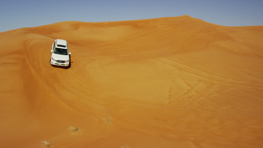 Dubai - April 2016: Aerial Drone Off road vehicles driving groups tourists across undulating desert sand dunes outside Dubai shot on RED DRAGON #18806387
