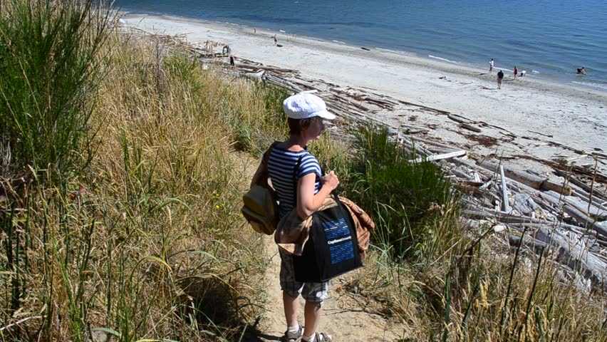 Middle age woman on sandy trail with nice ocean view at summer day in Vancouver, Canada.