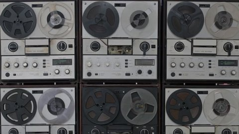 Many vintage magnetic reel to reel tape recorders playing all in the same time, synchronized, with spinning reels. Front view.