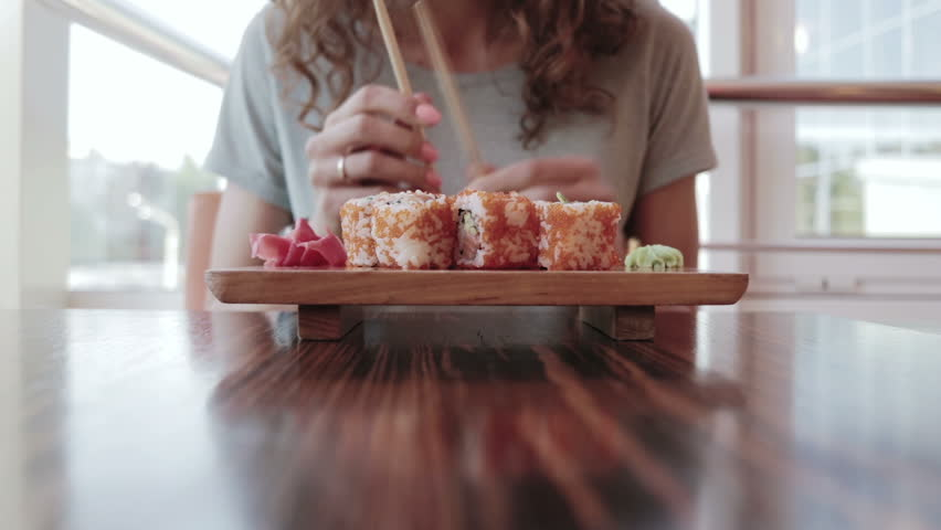Young woman in a t-shirt in a cafe eating rolls with chopsticks, close-up #18861191