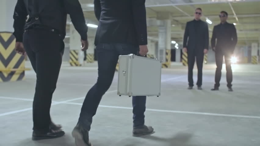 Slow motion tilt up tracking of confident Caucasian and African-American mafia men in sunglasses with money case in empty parking lot walking towards two gangsters then opening it for checking cash.