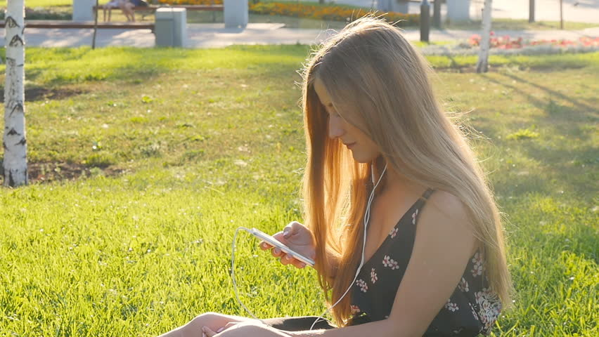 Young woman on grass with phone | Shutterstock HD Video #18886307