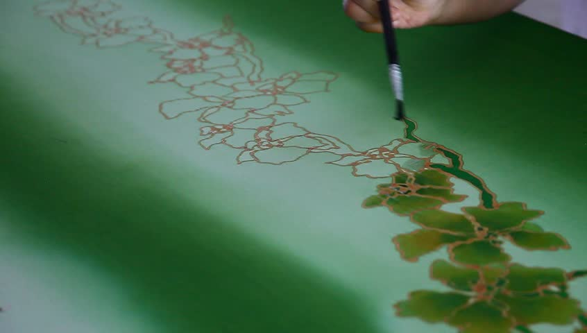 An artist coloring the batik fabric with floral motif