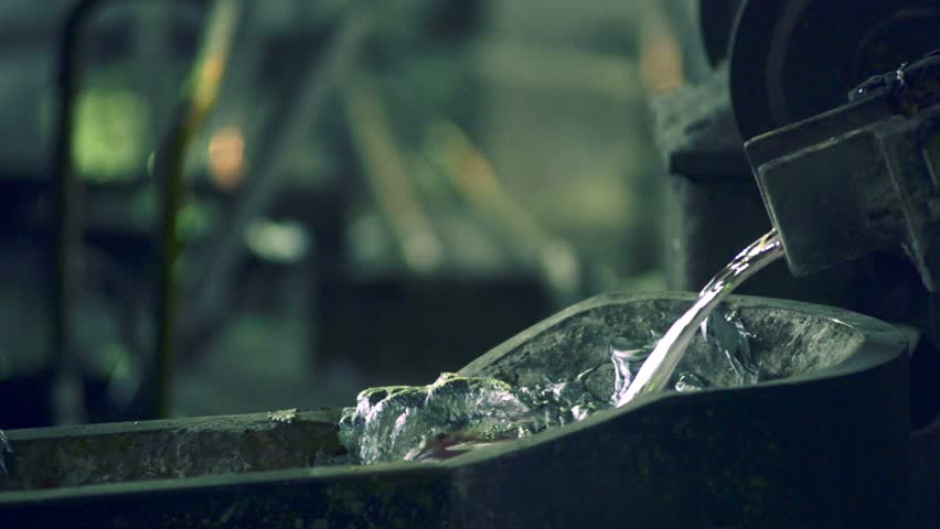 Liquid melt metal flows from the melting furnace, blurred background, close-up