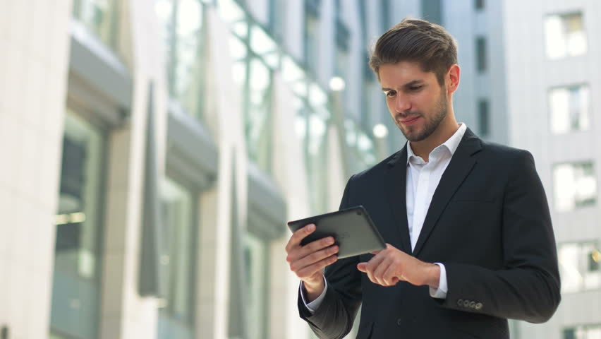 Handsome businessman read news on Tablet Computer, urban street public space