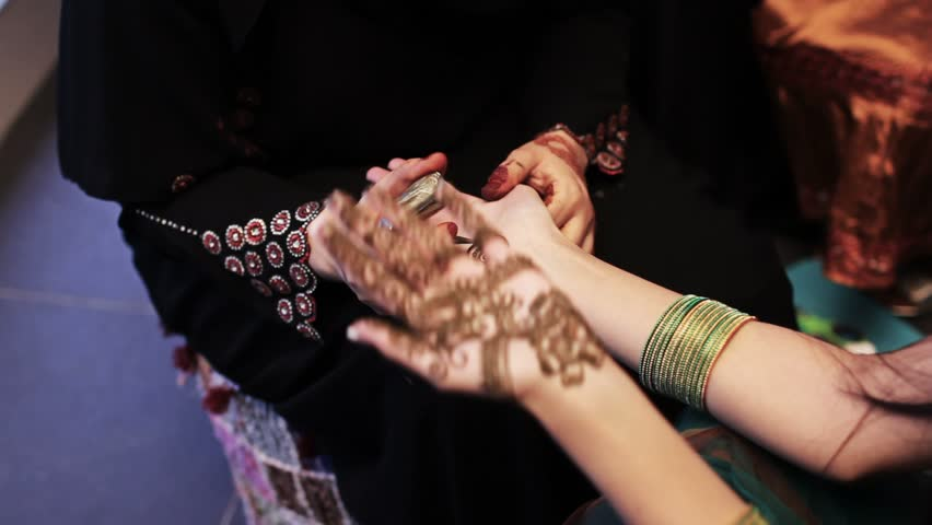 Henna being drawn onto hands