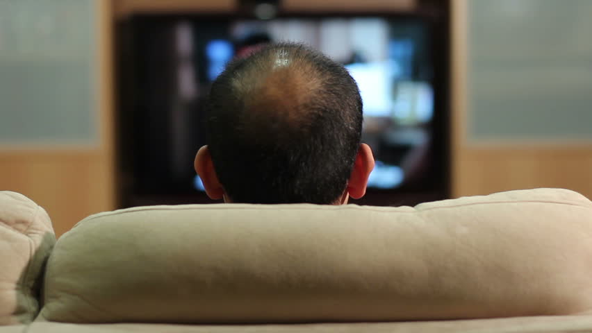 HD clip of a balding man watching an HDTV, turning it off and leaving.