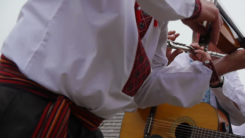 charismatic folk musicians playing energetic ethnic music in the mountains. Violin close up