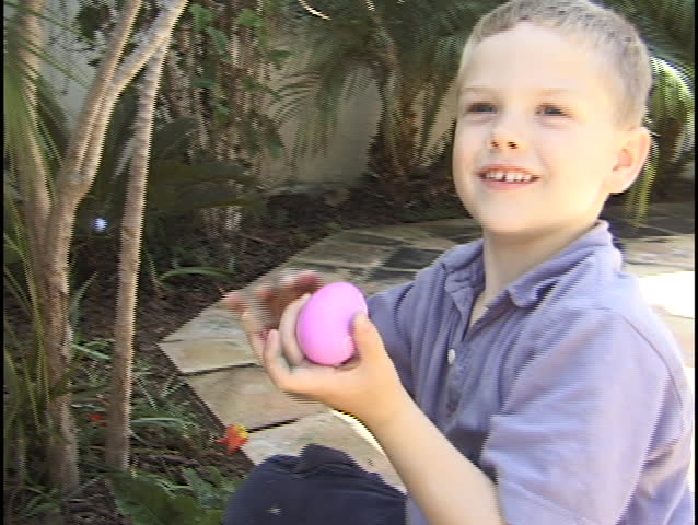 A young boy hunts for Easter eggs.
