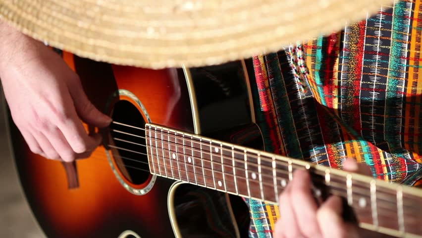 male hands playing on the strings of a guitar, Mexican in poncho and sombrero playing guitar, sambrero hat covers a person's face, hands guitarist guitar fingers on the fretboard, close-up