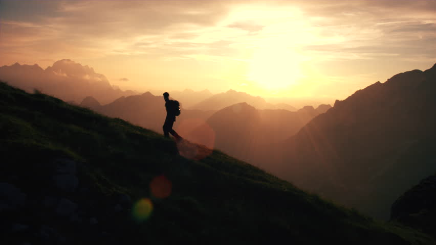 Aerial - Epic shot of a man hiking on the edge of the mountain as a silhouette in beautiful sunset (edited version)
