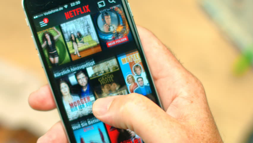 AACHEN, GERMANY - August 2016 : Netflix app on Apple iPhone 6s. Young man is browsing the movie video library what to watch.  | Shutterstock HD Video #18957221