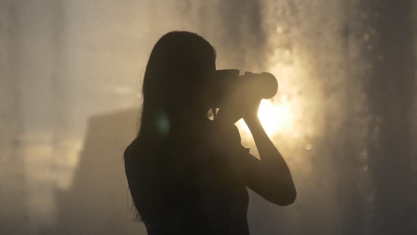 Silhouette of female photographer taking pictures of fountain water drops shining on sunset #18965677