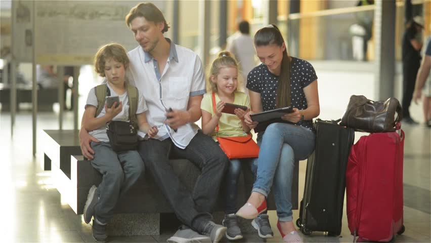 Family waiting for your flight or train and use the tablet and phones while sitting in waiting room of airport or railway station. | Shutterstock HD Video #18966427