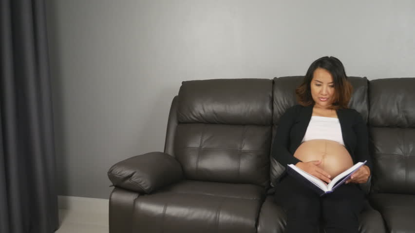 5568a60b8b Panning shot of pregnant woman sitting on sofa and reading a book. a. By  aeyaey. Stock footage ID  18991657. Video clip ...