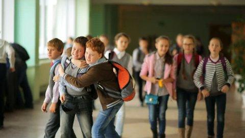 Russia, Novosibirsk, 2015: Children go by the school hallway during recess. School change. Two schoolmates. School weekdays. School in Russia
