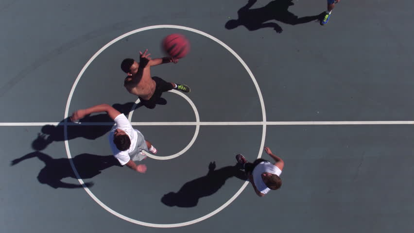 Friends playing basketball at park, overhead shot of tip off
