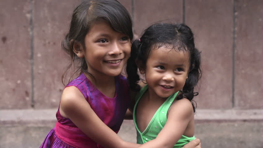 Portrait of young cute Asian girl hugging her sister and smiling. Children, family, happy people