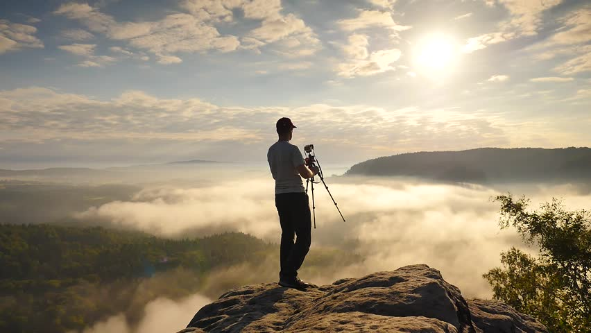 Photographer in grey t-shirt finished work and folding camera and tripod. Man stay on cliff edge above fog.  Dreamy fogy landscape, blue misty sunrise in a beautiful valley below | Shutterstock HD Video #19012597