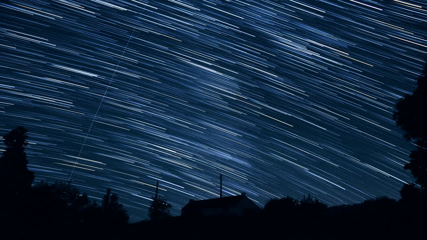 """Stars create trails in the sky and seem falling as meteors - Starry night sky in timelapse - ISS is appearing at 2""""17 - Looking to southwest from western Europe above an isolated house in countryside."""