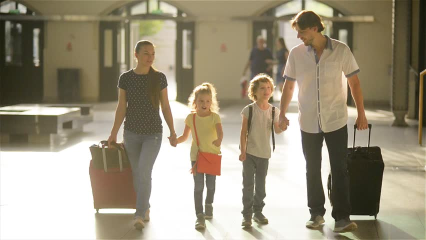 Parents and children are on the station with travel bag, happy family traveling