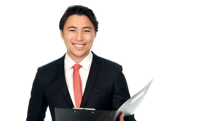 e39b4fa8fa39 An attractive businessman in a black suit and red tie, walking in front of  camera holding a clipboard. Smiling and looking at camera. White background.