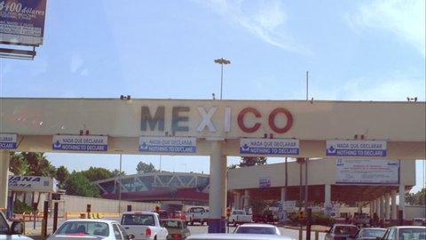 Day mpov thru drivers window toward mexico border checkpoint signs vague  reflection windshield tilt up with sign, nothing to declare english spanish  back down palm trees