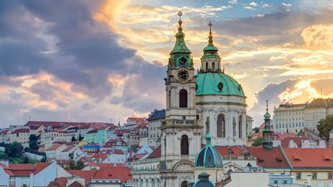 sunset behind St Nicolas timelapse in Mala Strana in Prague. Colorful cloudy sky. View from Lesser Town Tower