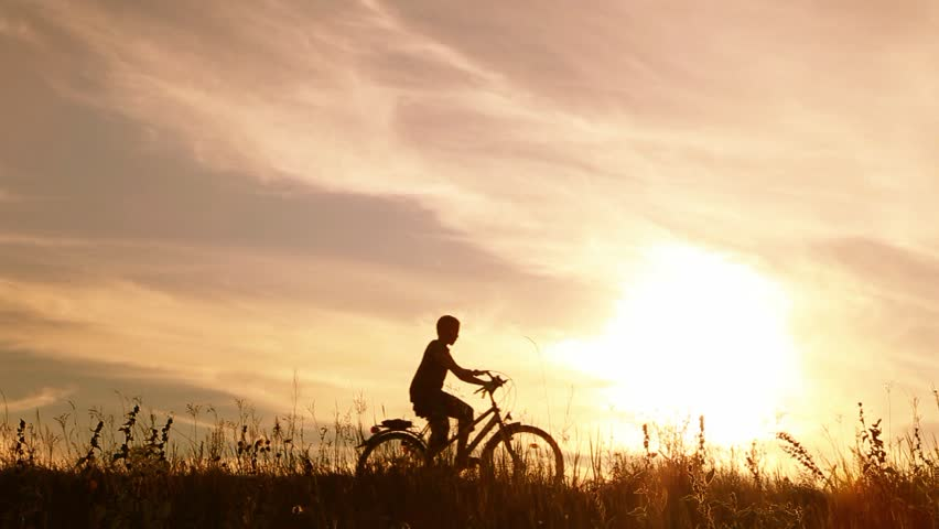 Little kid riding bike in summer meadow landscape at beautiful sunset sky background. Silhouette of anonymous caucasian small boy of 9 years old sitting on bicycle in countryside area. Real time video