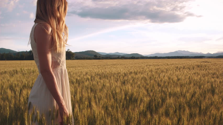 Young woman standing in the wheat field watching sunset looks into the camera | Shutterstock HD Video #19089757