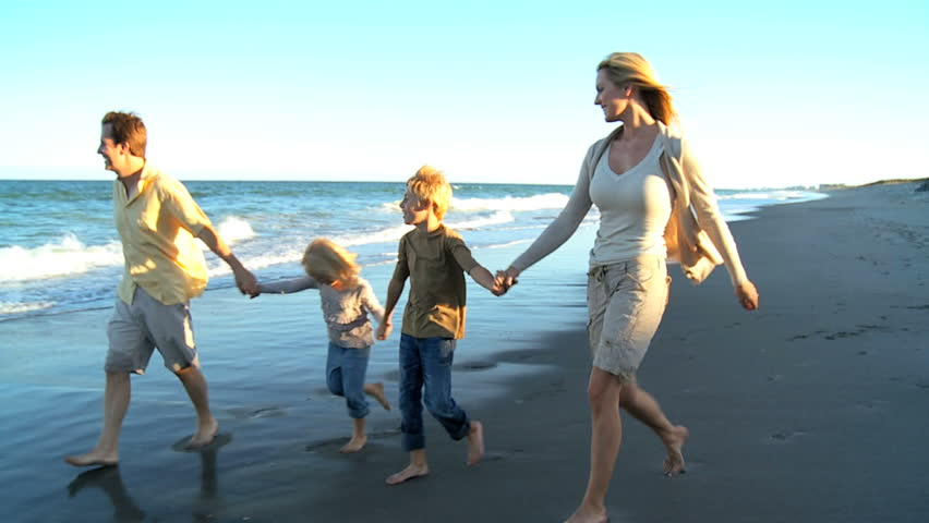 Happy young family group walking along the beach at dusk | Shutterstock HD Video #1910752