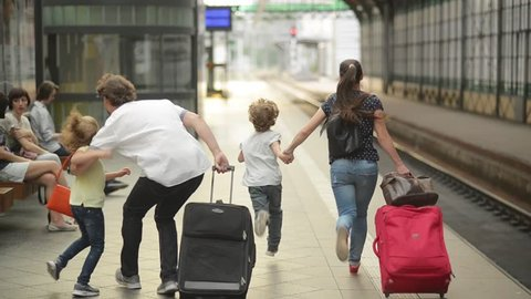 Young family of two spouses, son and daughter, running in the railway station, father holding daughter, parents and children traveling and be late