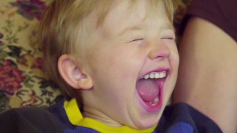 close up on adorable little boy as he yells, laughs, and screams in joy and excitement