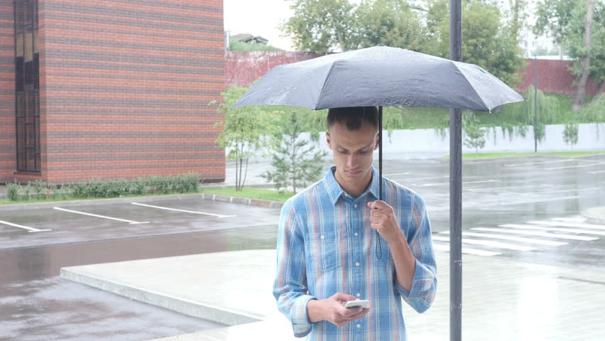 Talking on Phone, Standing Under Umbrella during Rain | Shutterstock HD Video #19155628